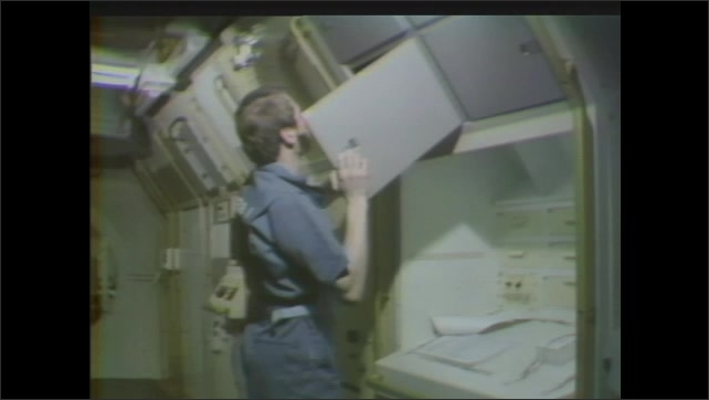 1980s: American flag ripples in breeze amid crowd of people. Astronaut opens compartment. Spacelab placed in orbiter.