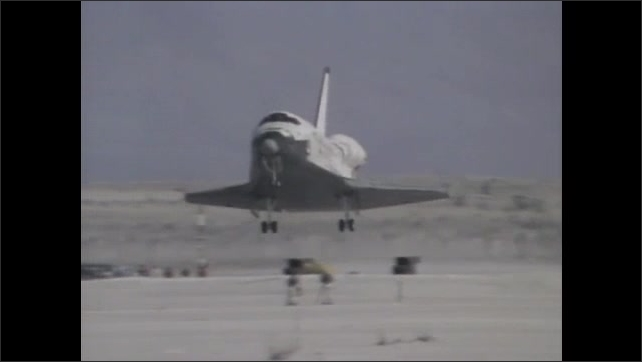 1980s: Astronaut-researcher pulls sample from storage contraption. Flying insects in contained area. Space shuttle lands at White Sands Missile Range in New Mexico. Space shuttle launches.