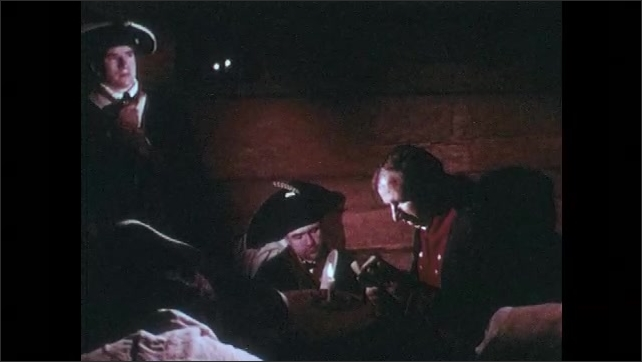 1970s: Soldiers huddle around lit candle. Soldier reads from book.