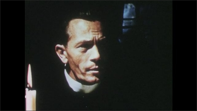 1950s: Priest and man sit at table and talk. Priest looks out over candlelight. Man nods head and speaks. Men shake hands. Priest stands and leaves table.