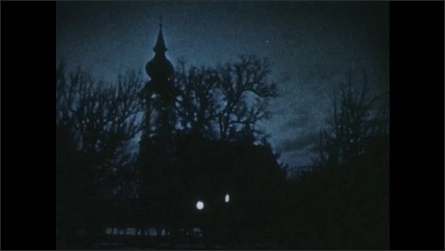 1950s: Shadow of church and steeple against clouds and moonlight. Light spills from church window on dark night.