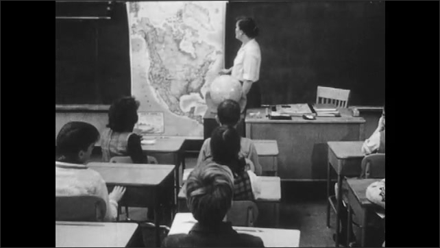 1960s: Classroom.  Children sit.  Teacher points at map and speaks.
