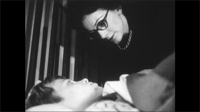 1960s: Mother leans over little boy laying in bed.  Woman speaks.  Boy rolls onto his side.