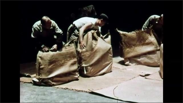 1960s: Men stack bales of silk in bag. Men put paper cover over stack of silk. Men cover bags with woven cloth. Hands sew cloth over bag.