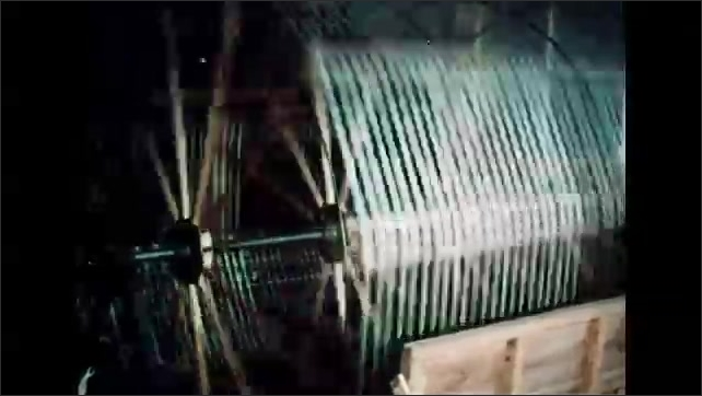 1960s: Bales of silk lifting onto truck. Silk thread spinning on machines. Large machine spinning silk. Bobbins of thread on machine.
