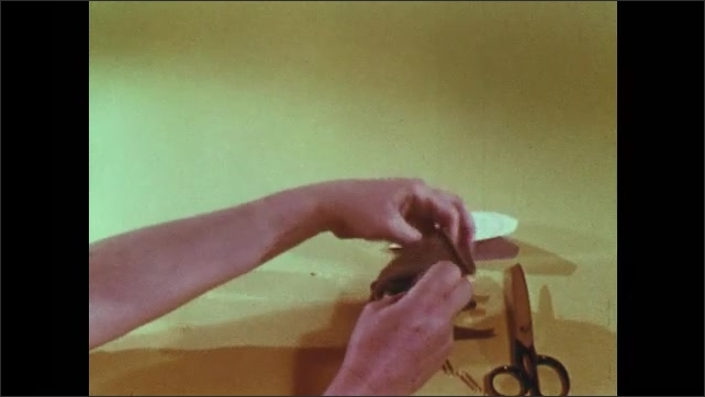 1950s: Person with sewn sock for hand puppet on hand makes cuts on sock with scissors. Person pulls paper from out of sock then places sock inside out on other hand.