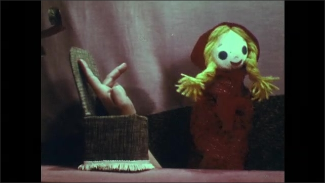 1950s: Hand puppet of Red Riding Hood sits in chair on stage while a hand appears. Red Riding Hood and hand trade places and Red Riding Hood leaves. Hand puppet of man performs on stage.