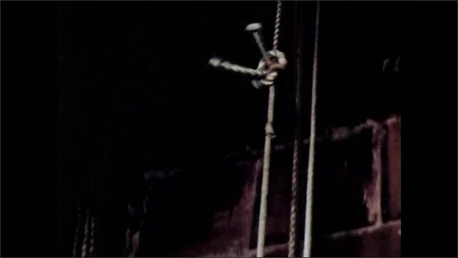 1960s: Play.  Actor flies through the air.  Audience smiles.  Boys control pulley with ropes.