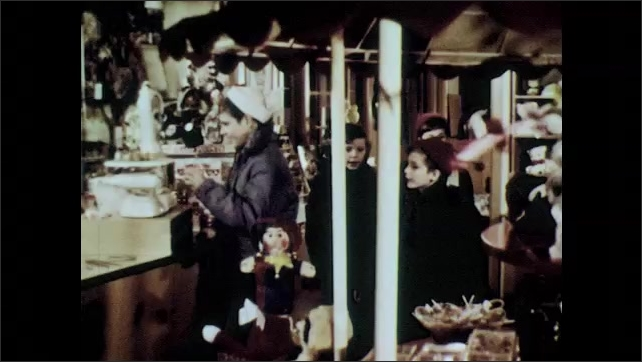 1960s: Old man shovels snow.  Little boys go into candy store.  Boy picks up nutcracker and speaks.