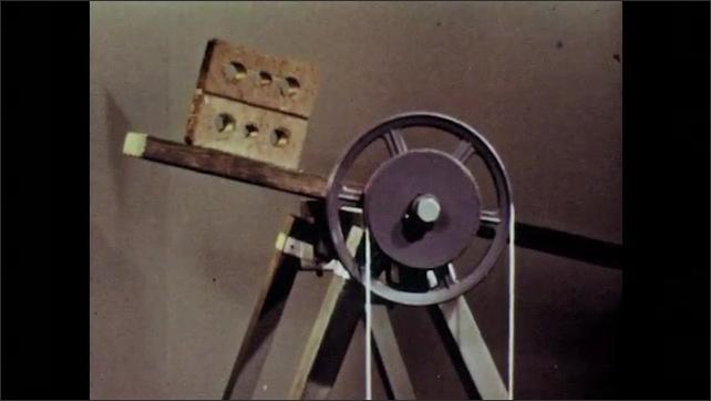 1960s: Pulley raises brick.  Bricks balance on board.  Hand pulls rope.