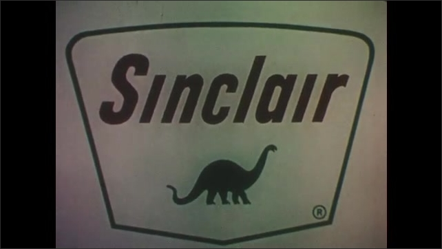 1960s: Dinosaur model in primordial landscape. Car roars down road. Sign for Sinclair Dino Supreme gasoline. Car drives down twisty road with man driver smiling. Sinclair gas sign.