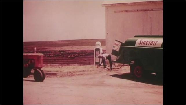 1960s: Rural sunrise. Sinclair fuel truck drives on to farm. Farmer drives up on tractor. Sinclair truck fills farm gasoline pump.