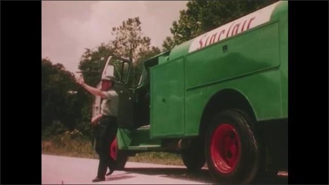 1960's: Farmer on tractor removes hat and wipes face. Farmer waves to Sinclair fuel delivery man in truck. Sinclair man opens truck doors and helps farmer maintain tractor.