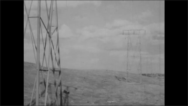 1940s: Electrical current generators spin in power plant. Power lines in desert.