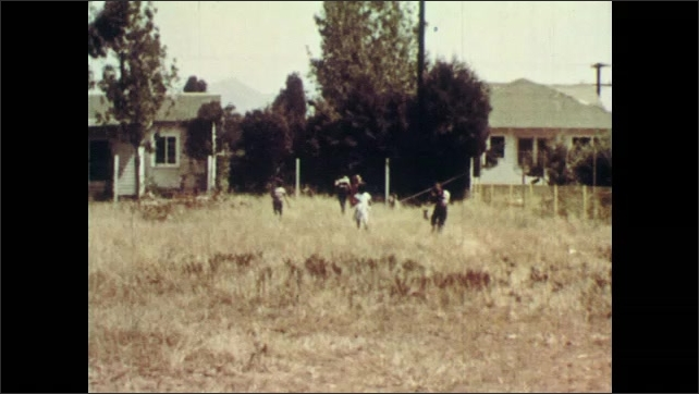 1950's: All the children and all the dogs run happily together through the vacant lot. New girl smiles and hugs Skipper the dog.