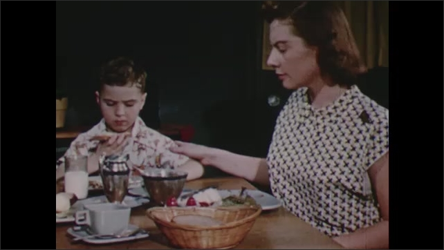 1950s: Boy sits at table, chews, shrugs shoulders. Woman hands bread to boy, boy takes bite. Man talks to boy.
