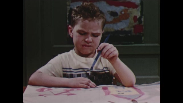 1950s: Girl paints name on paper. Boy holds paintbrush, looks confused.