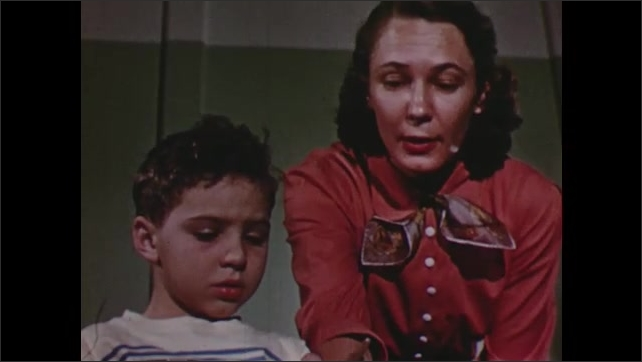 1950s: Woman looks and smiles. Woman walks over to children at table, talks to boy, helps boy paint letter. Woman rolls name chart over, points to name.
