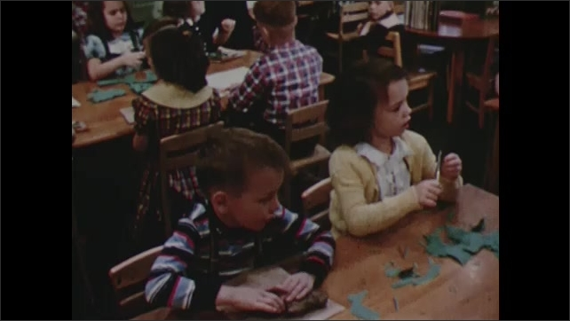 1950s: Children in classroom, sit at desks making arts and crafts. Woman walks around room checking on students.
