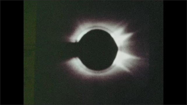 1970s: UNITED STATES: artificial eclipse of sun. Photographs of corona on sun. Crewman operates switches on control panel