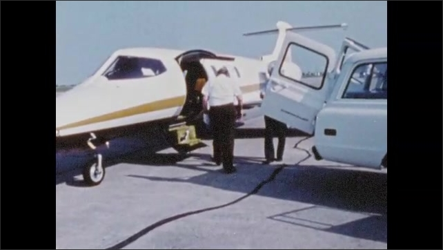 1970s: UNITED STATES: parasol team finalise parasol day before space flight. Parasol in flight canister. Small plane on tarmac.