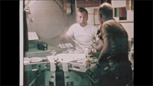 1970s: UNITED STATES: astronauts eat in space. Astronauts relax during meal.