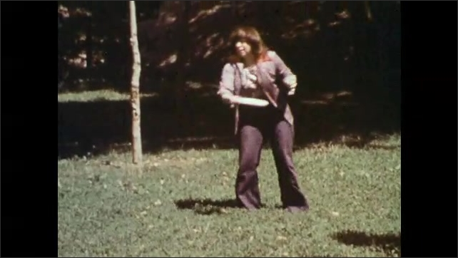 1980s: woman in pantsuit with necklace catches and throws Frisbee in grassy part of park near trees and bushes.
