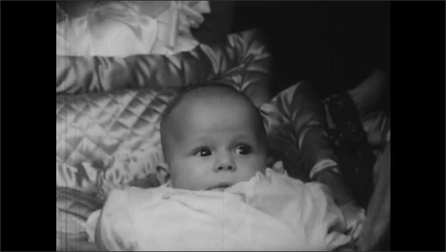 1940s: Lady and Queen stand, fawn over baby in bed, look skeptical, surprised, happy, smile. Baby looks around. King, Queen talk. People gather.
