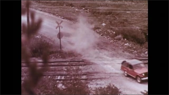 1970s: Cartoon cow sits in back half of car, watches flask fall onto railroad tracks. Jeep speeds over railroad tracks, stops in dirt lot.