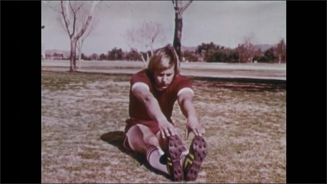 1970s: UNITED STATES: footballer reaches toes in seated position. Man stretches legs. Boy stretches back of legs