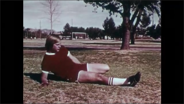 1970s: UNITED STATES: man in park stretches thigh muscle. Stretching and flexibility exercises.