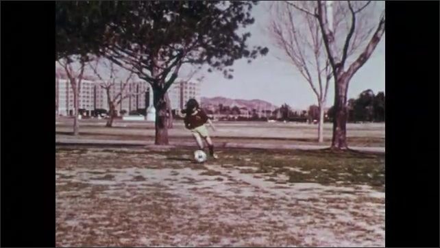 1970s: UNITED STATES: girl dribbles ball in slow motion. Girl practices football in park