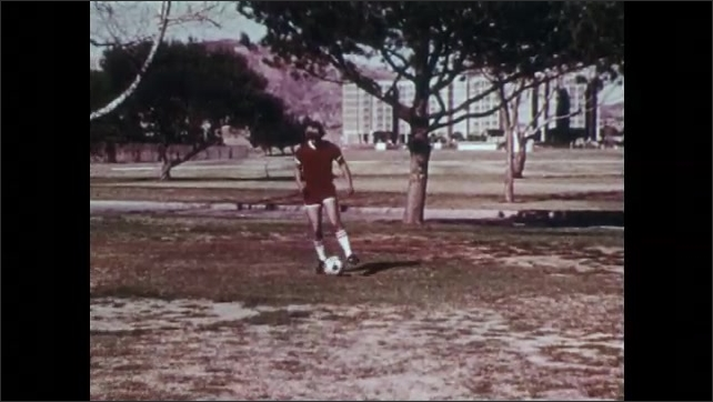 1970s: UNITED STATES: boy slips on ground in slow motion. Boy practices falls