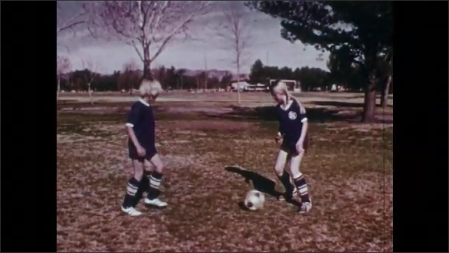 1970s: UNITED STATES: girl and boy practice football skills in park. Ball control skill development. Footballers run on spot