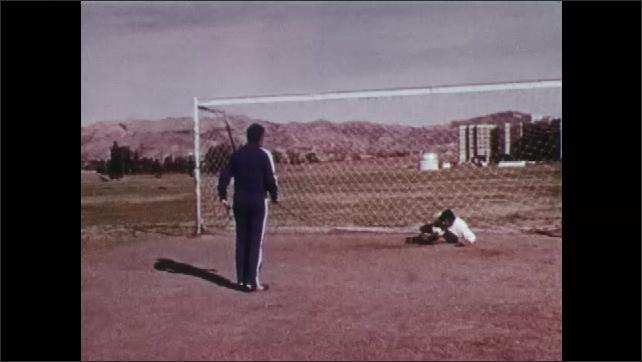 1970s: UNITED STATES: goalkeeper kneels in net.