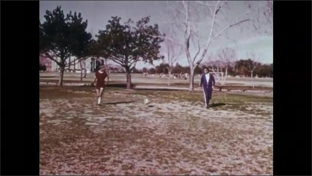 1970s: UNITED STATES: slow motion of men dribbling football in park. Men kick ball in park