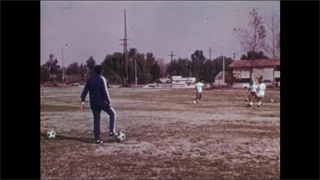 1970s: UNITED STATES: men kick ball to each other. Defensive position in football. Two on two tactical exercise. Slow motion of players dribbling ball