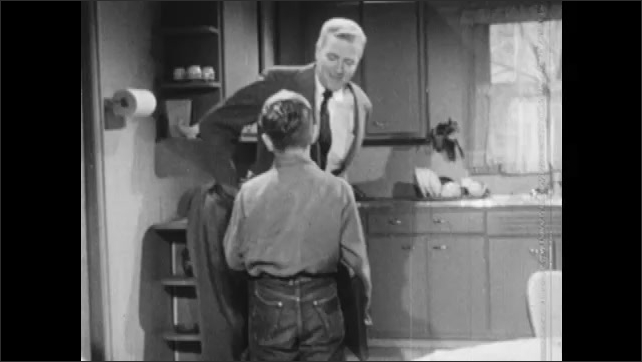 1950s: Woman and girl working in kitchen, man enters. Boy stands from table, greets man. Woman and girl working, man kisses woman and girl.