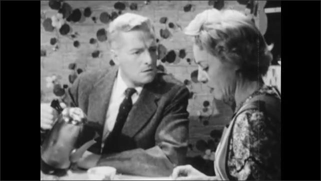 1950s: Woman talks to man at table. Man and woman talking at table. Woman talking.