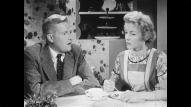 1950s: Woman talks to man at table. Man and woman talking at table.