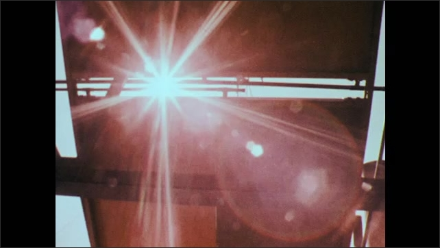 1970s: UNITED STATES: sunlight streams through gaps in structure. Man speaks to camera.