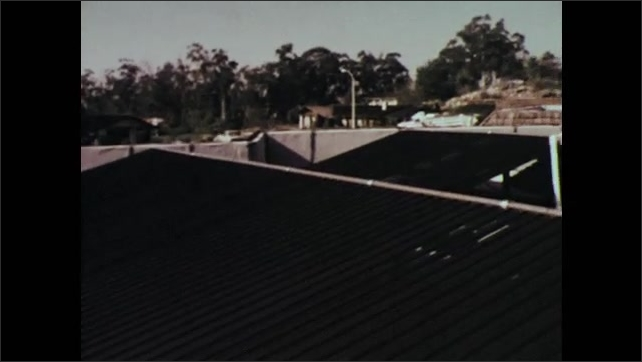 1970s: UNITED STATES: houses in suburb. Space saving systems in buildings. Roof of building. Conventional versus solar charged system.