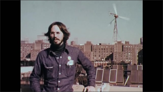 1970s: UNITED STATES: man on roof of city building looks across view to windmill.