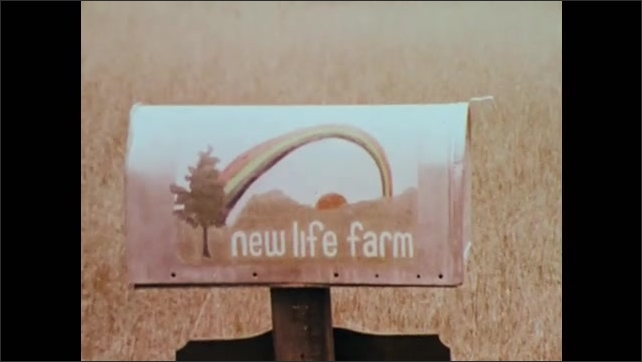 1970s: UNITED STATES: mural painted on city wall. New Life Farm sign. New Life Farm sign. Building on farm.