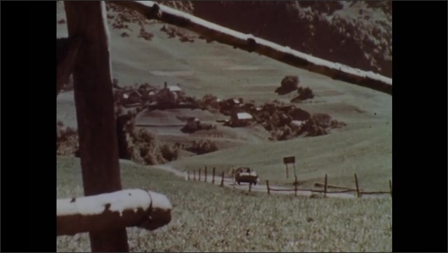 1960s: Canal near buildings in city. Rolling hills and mountains. Family plays ball outside home. Car drives through rural countryside. Snowcapped mountains. Medieval castle and bridge near river.