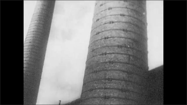 1960s: EUROPE: portrait of Stalin. Large brick chimney. Man stokes fire
