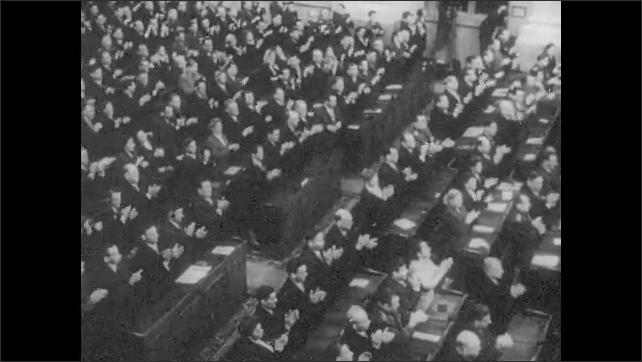 1960s: EUROPE: congress members stand and applaud in meeting. Newspaper headlines. Propaganda publishing