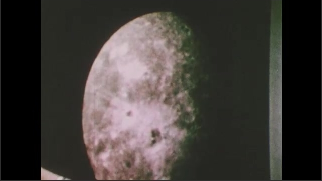 1980s: Men look at image of Uranus' moon Oberon. Man gestures at Oberon. Man speaks.