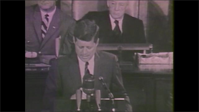 1980s: Men sit in audience. Man looks up. Man in audience raises hand. John F. Kennedy takes floor of senate and gives speech. Richard Nixon waves to crowd and sits down. Ronald Reagan gives speech.