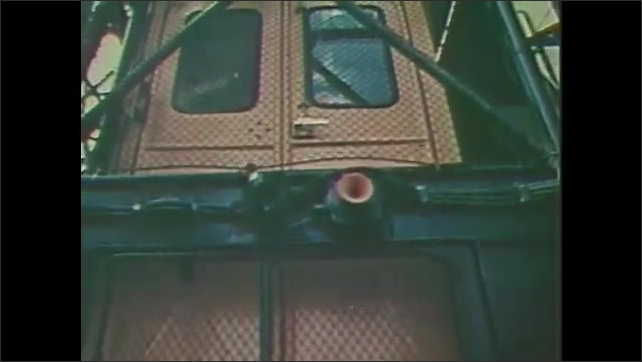 1980s: Astronauts in space suits ride elevator up to enter rocket. Rocket launches into space.